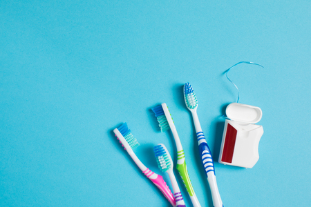 four multi-colored toothbrushes on a blue background Stock Photo