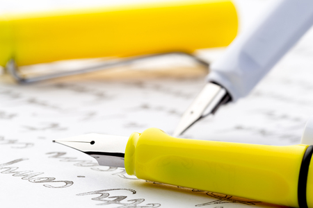 yellow and white fountain pens on a letter