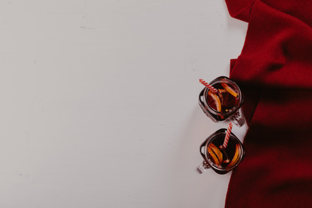 Mulled wine in mugs with scarf on white wooden table