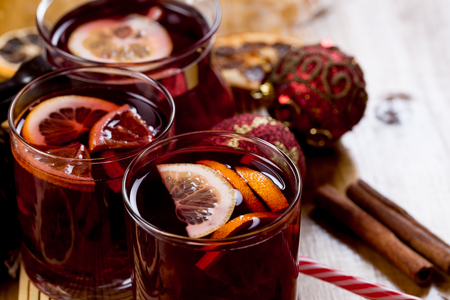 Mulled wine in glasses with spices on wooden background,top view
