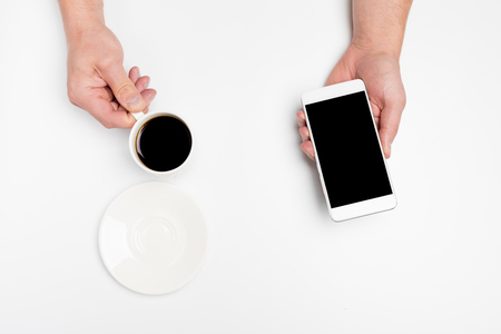 Hands holding a cup of coffee and White Smart phone, isolated on white