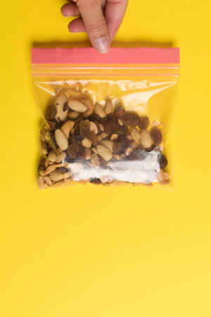 Plastic zip package for food storage. Healthy snack nuts in a closed package on yellow background Foto de archivo