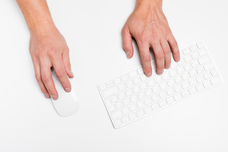 A man hand hold a wireless mouse with keyboard isolated white.