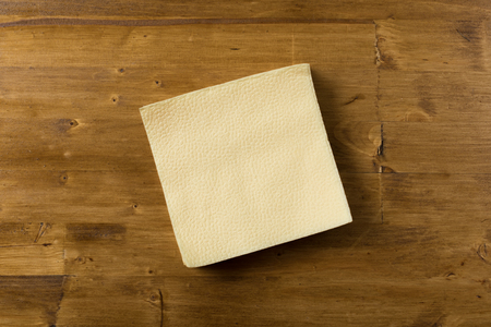 yellow paper napkin on wooden background