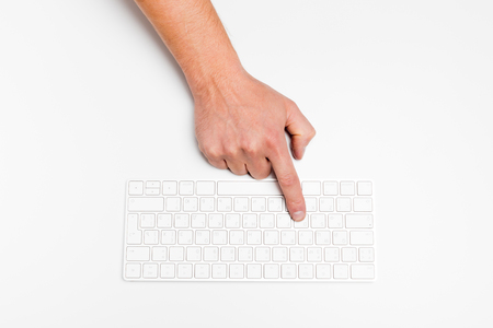 A man hand using a wireless keyboard isolated on white. 版權商用圖片
