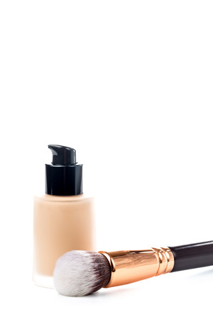 Close-up of flat makeup brush with liquid foundation tube isolated on white
