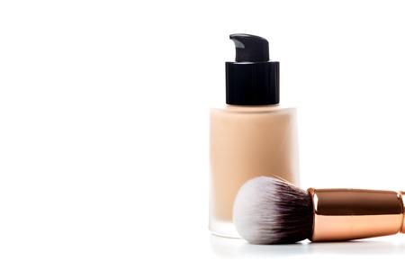 Close-up of flat makeup brush with liquid foundation tube isolated on white