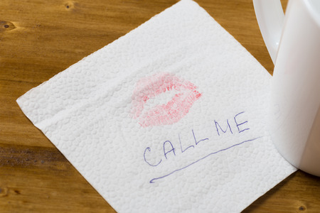 Napkin with a kiss and coffee cup on wooden background 版權商用圖片