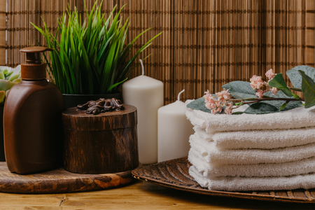 Spa still life with aromatic candles, flower and towel.