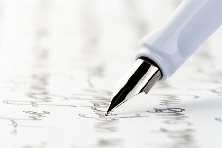 pluma estilográfica blanca escribiendo una carta Foto de archivo