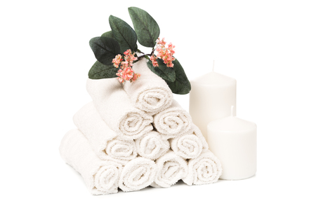 set of white roll towels with flowers and candles isolated on white