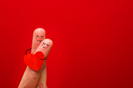 Happy couple in love with painted smiley holding red heart - Image