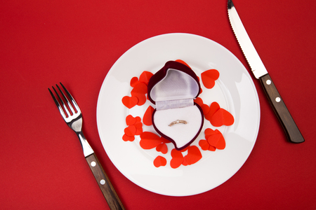 Box witha ring, table setting on a red background. Concept Valentine's Day. - Image