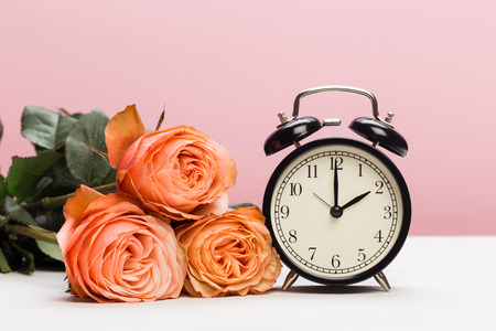 rose roses and clock on pink background, daylight saving Stock Photo