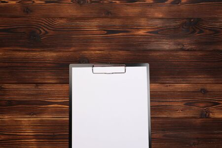 Clipboard with white sheet on wood background. Top view. - Image Stock Photo