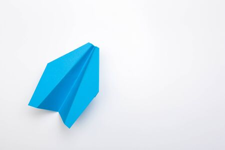 Flat lay of blue paper plane on white background with text space. - Image
