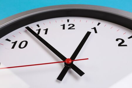 """Closeup wall clock set on blue background. The concept of """" The time is going on."""" Top view with Selective focus. Copy space. - Image"""