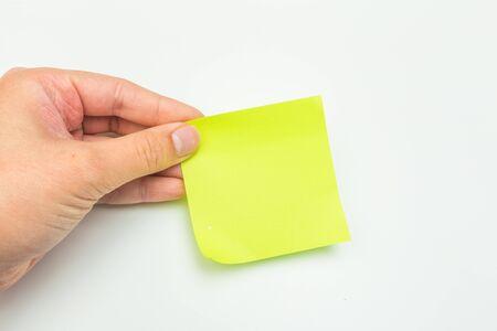 Nota post-it verde con la mano sobre fondo blanco - Imagen Foto de archivo