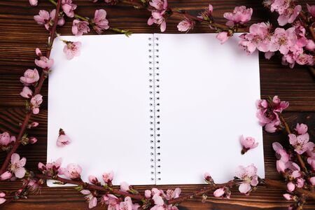 White paper sheet and sprigs of the apricot tree with flowers on wooden background. Place for text. The concept of spring came, happy easter, mother's day.Top view.Flay lay. Copy space. - Image