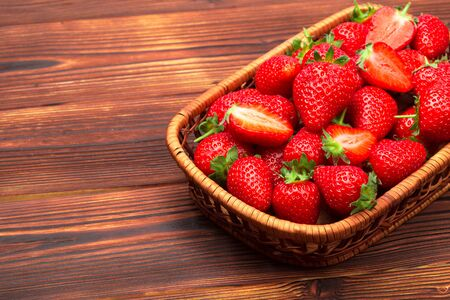 Juicy washed strawberries in wooden bowl on kitchen table. - Image Reklamní fotografie