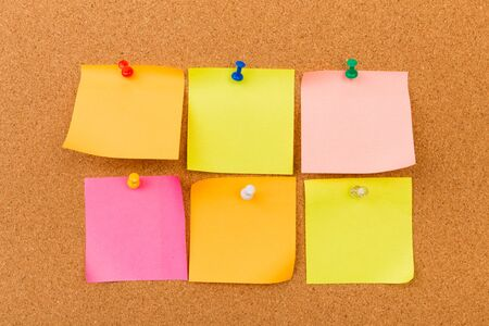 Tablero de corcho con notas en blanco coloreadas fijadas - Imagen