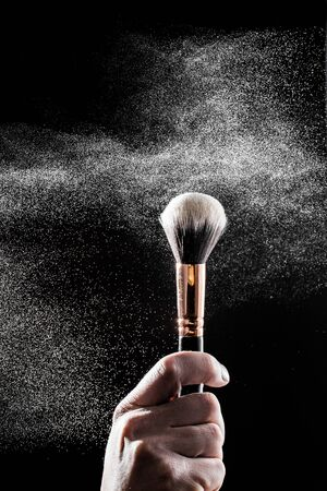thick black brush in motion and loose powder particles scattered around  - Image
