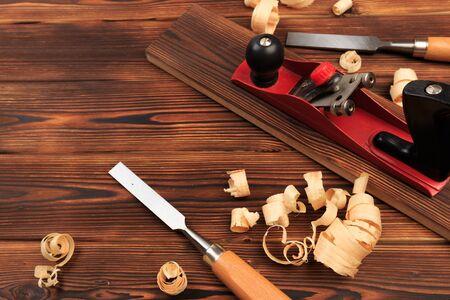 Plano de cinceles y aserrín sobre una mesa de madera - Imagen Foto de archivo