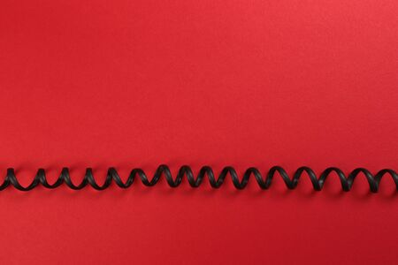 Curl black wire on red background - Image