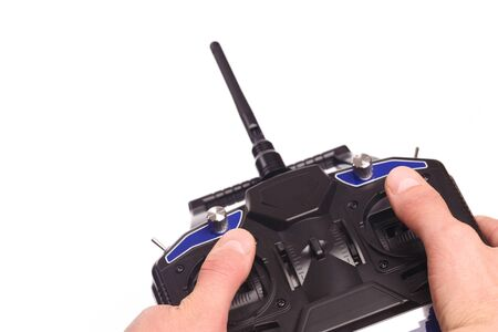 mans hands holding remote control with joysticks and antenna  isolated on white background - image