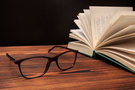 Open book with glasses on black  background. - Image Фото со стока