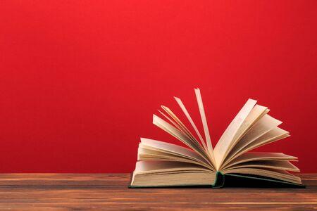 Libro abierto sobre fondo rojo. lugar de texto - Imagen Foto de archivo