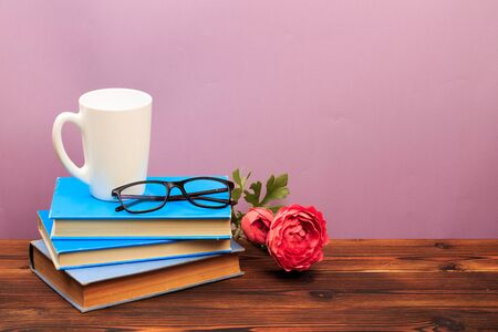 pile of old books with mug ang glasses panorma, good copy space on pink background - Image Reklamní fotografie