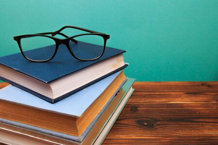 pile of old books with glasses panorma, good copy space on blue background - Image Reklamní fotografie