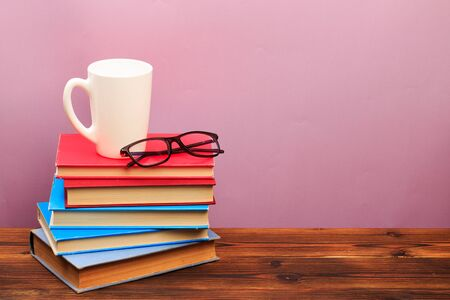 pile of old books with mug ang glasses panorma, good copy space on pink background - Image
