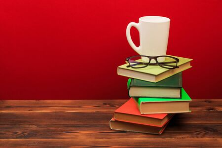 pile of old books with mug , panorma, good copy space on red background - Image