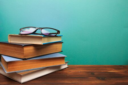pile of old books with glasses panorma, good copy space on blue background - Image
