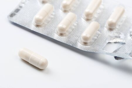 Pile of white capsules probiotic powder inside. Copy space. High resolution product. Health care concept Reklamní fotografie