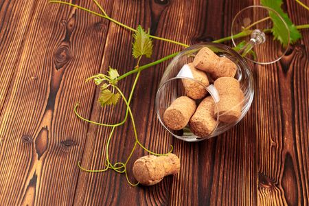 glass of wine with cork on wooden background - Image
