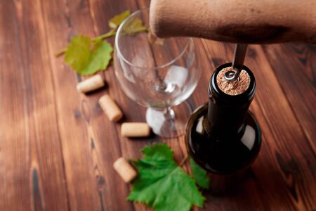 Tire-bouchon et bouteille de vin sur la planche