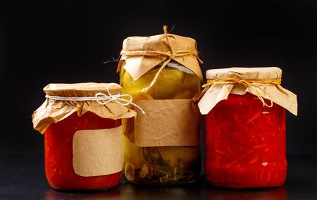 glass bottle with preserved food on black background - Image Banco de Imagens - 129608082