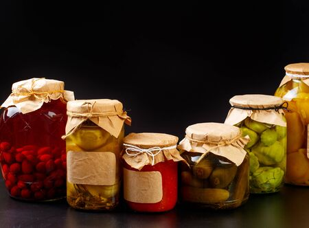 glass bottle with preserved food on black background - Image