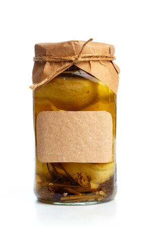 glass bottle with preserved food on white background