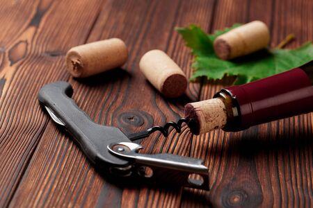Korkenzieher und eine Flasche Wein auf dem Brett