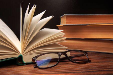 Offenes Buch mit Brille auf Buchhintergrund. - Bild