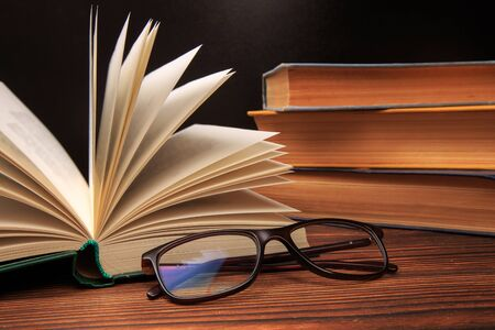 Open book with glasses on books background. - Image