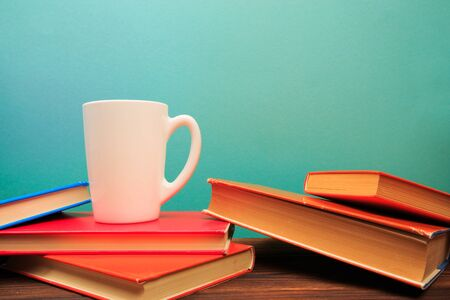 pile of old books with mug , panorma, good copy space on blue background - Image