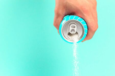 hand holding soda can pouring a crazy amount of sugar in metaphor of sugar content of a refresh drink isolated on blue background in healthy nutrition, diet and sweet addiction concept 写真素材