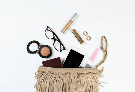 Fashion concept : Flat lay of brown leather woman bag open out with sunglasses and smartphone on white background.