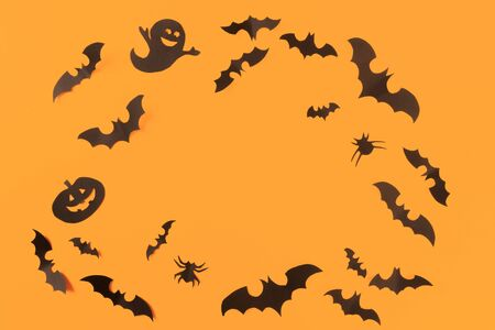 Halloween paper decorations on orange background. Halloween concept. Flat lay, top view, copy space