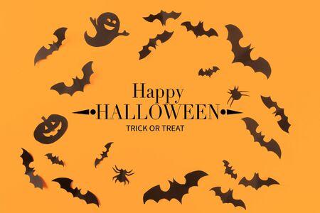 Halloween-Papierdekorationen auf orangem Hintergrund. Halloween-Konzept. Flache Lage, Ansicht von oben, Kopienraum